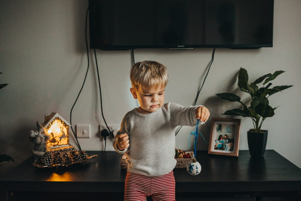 little boy holding a Christmas baubles