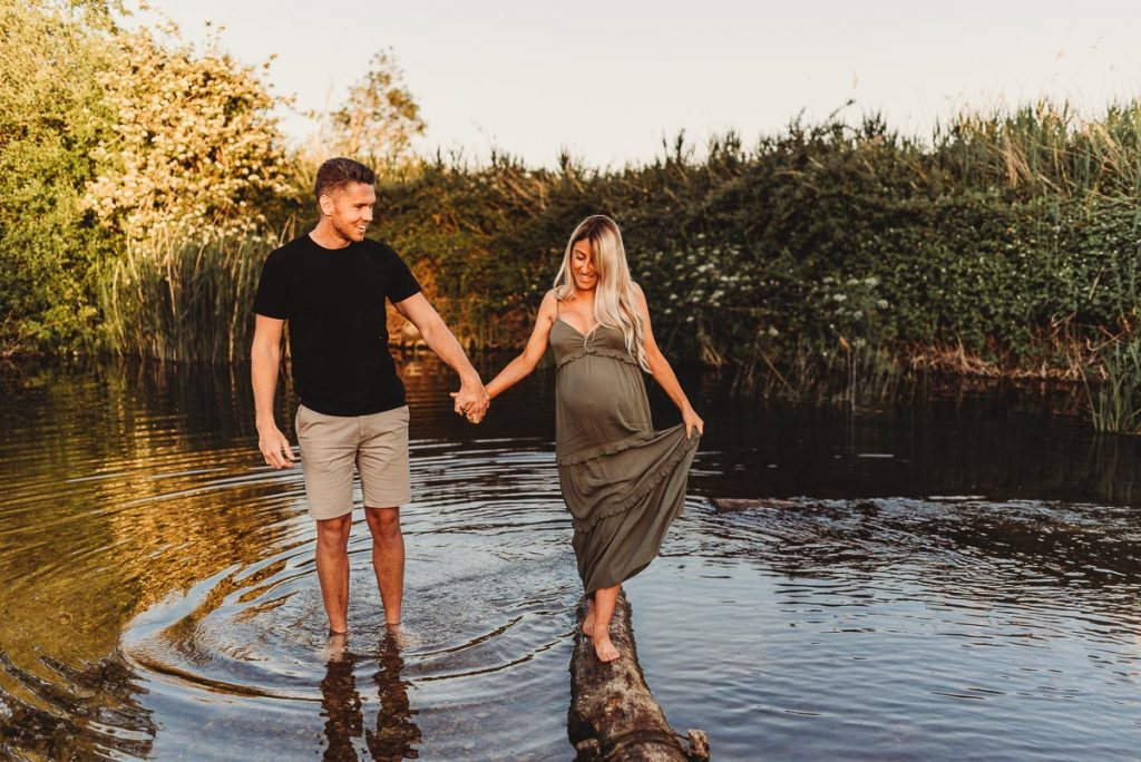 pregnant woman walking a long a log in the river holding her husbands hand