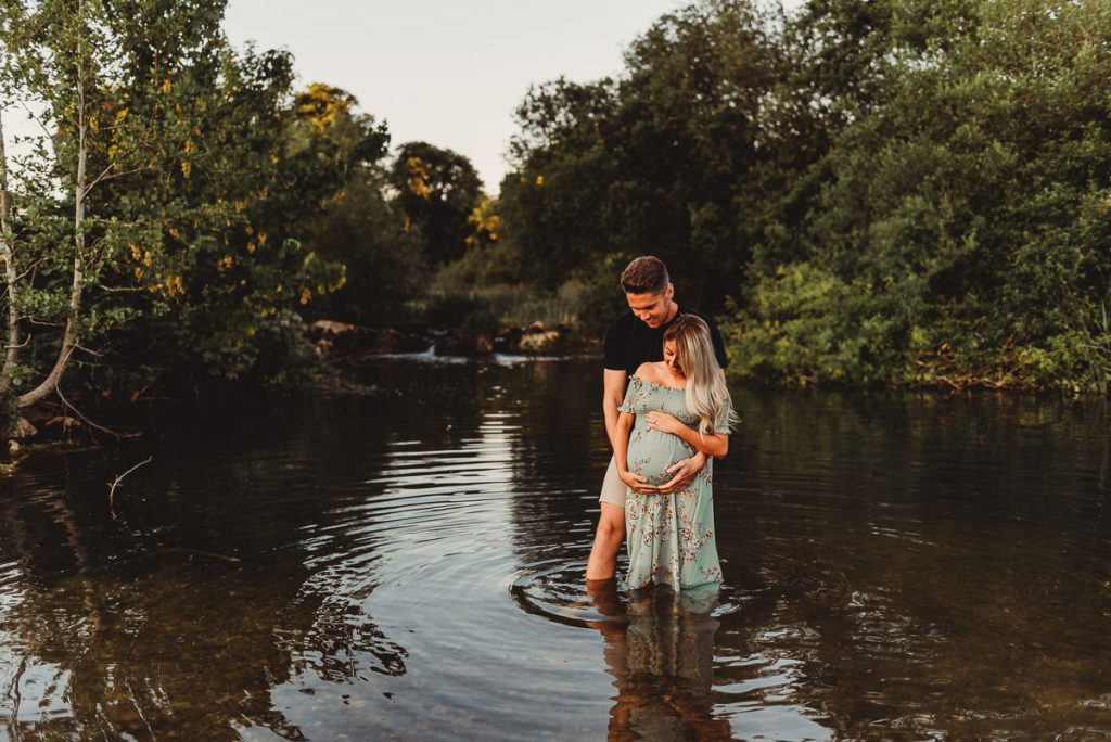 man and woman standing in a river with their hands on her pregnant belly