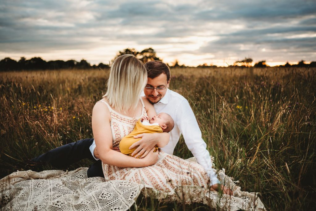 mother and father cuddling their newborn baby in a field of long grass at sunset