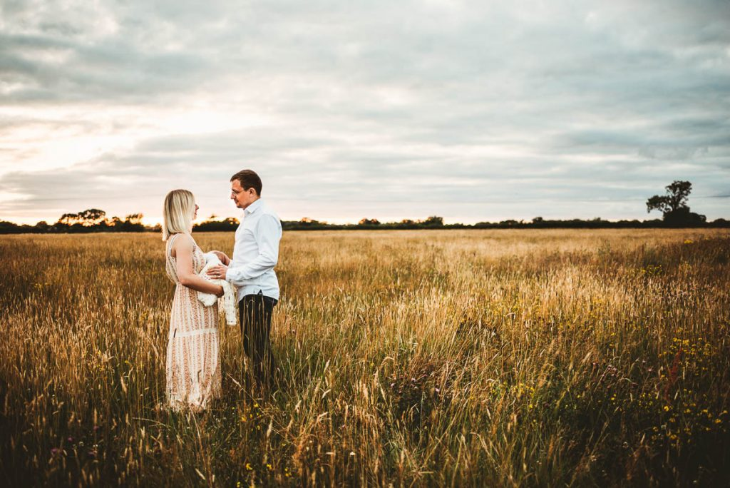 mum and dad facing each other in a golden field. Their newborn baby is between them