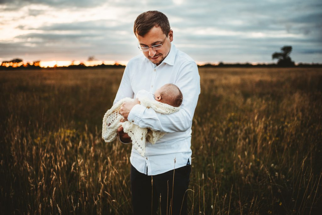 man holding his newborn baby boy in a field during sunset. Outdoor newborn photography session