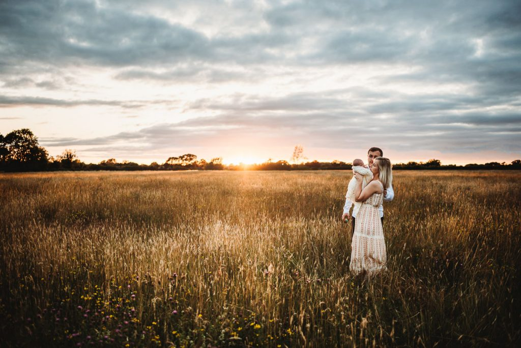 mum and dad with their newborn baby against a dramatic cloudy sky and orange sunset