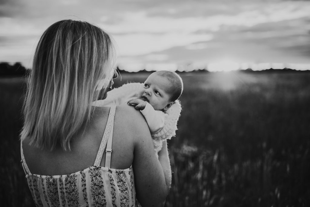 mother and newborn baby in a field during sunset