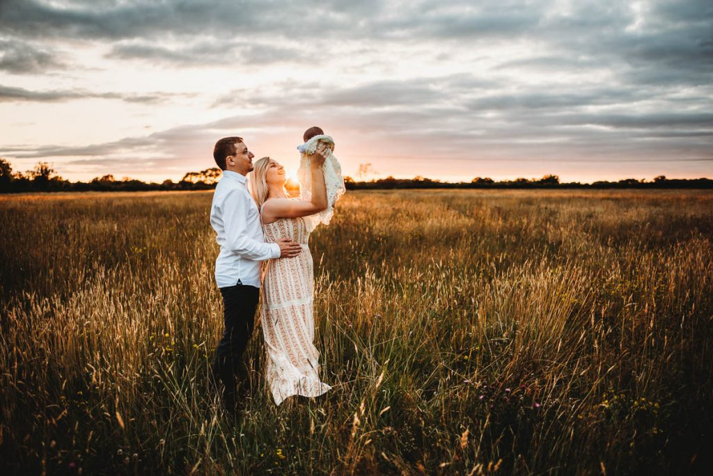 mum and dad holding their newborn baby up to the sky at sunset