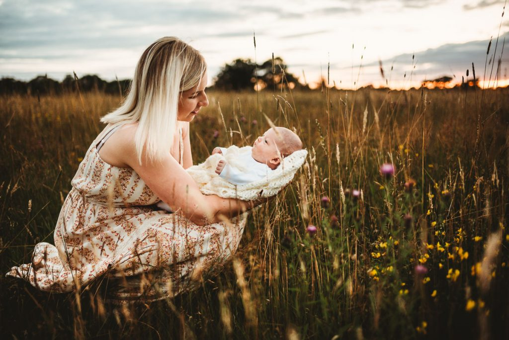 mother kneeling down in a long grassy field with her newborn baby in her arms